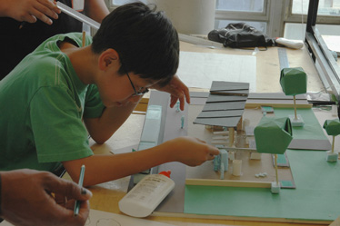 A Summer CAMP participant examines his model of a Cincinnati streetcar stop.